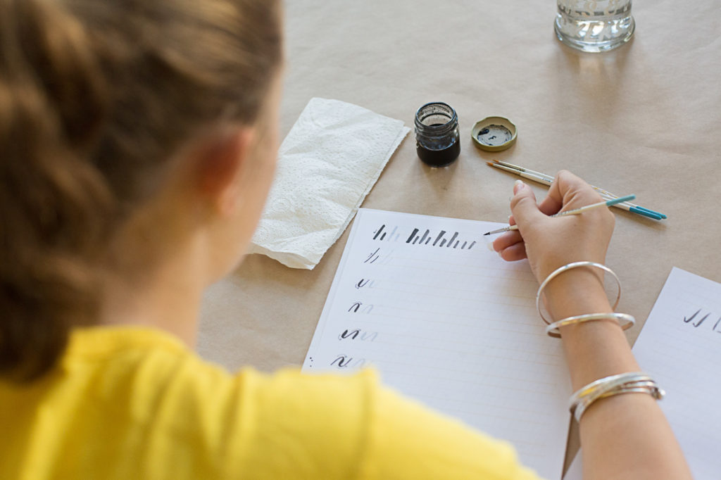 Student writing calligraphy drills with a brush