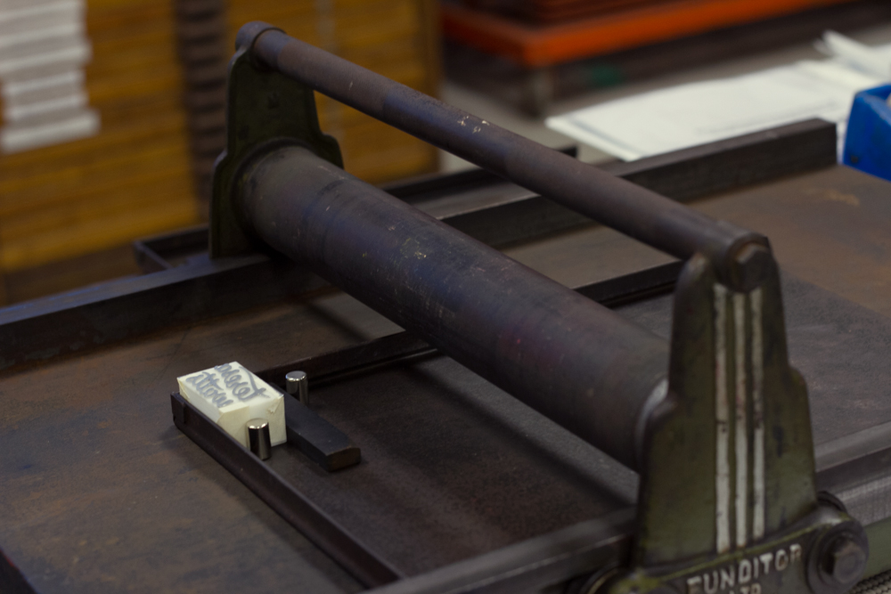 This proofing press has a handle with a roller attached, which is rolled over the paper and forme to create the print. I think this type of thing would be the easiest to DIY?