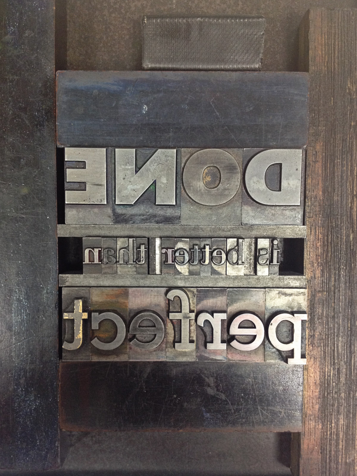 Metal type set in a forme held together with magnets. It's tough trying to think in mirror image!