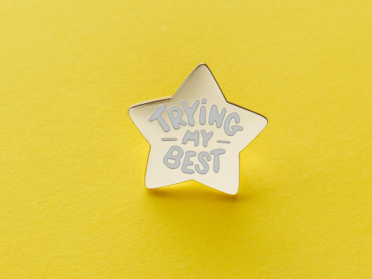 "Star shaped pin that says ""trying my best"""