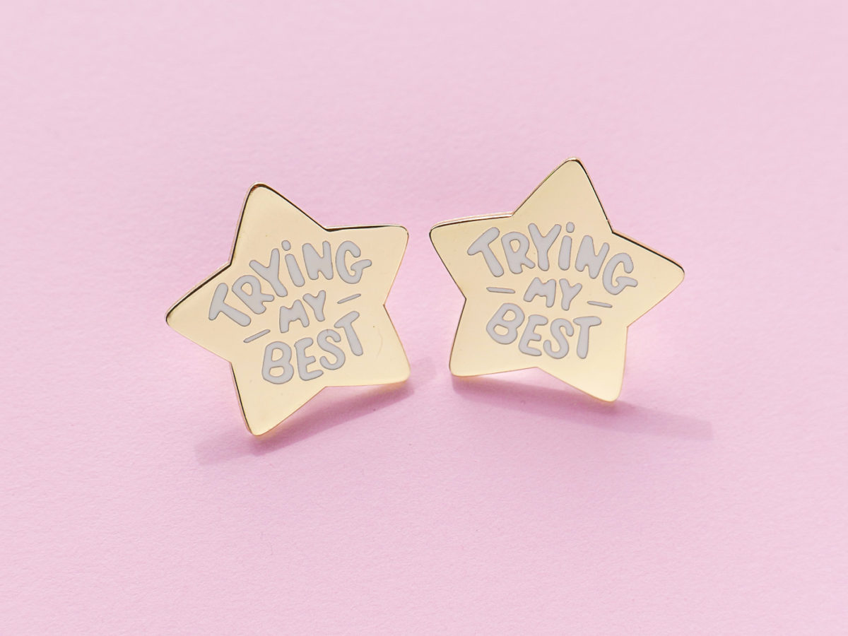 "2 star shaped pins that says ""trying my best"""
